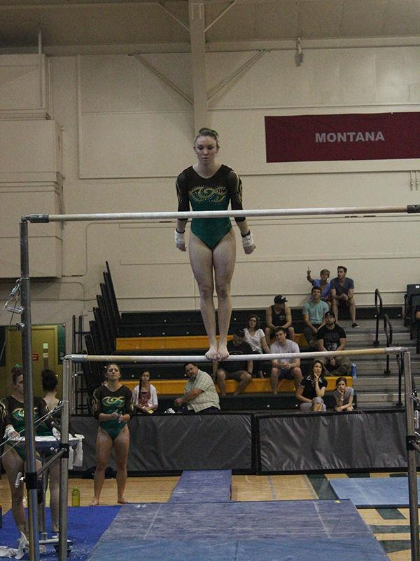 Junior Alyssa Anderson performs the uneven bars in a meet against Utah State University in the Hornets Nest on March 15, 2015.