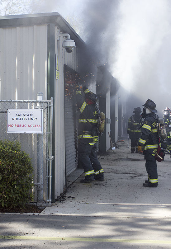 A firefighter uses an eletric hand saw to cut open the a door of a shed located behind the track as smoke pours out on Tuesday, March 17, 2015.