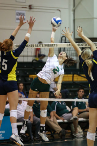 Sacramento State middle blocker Courtney Dietrich strikes the ball between two Northern Arizona University blockers on Saturday, Sept. 26, 2015 at the Nest. Dietrich lead the team in blocked shots with three in the match.