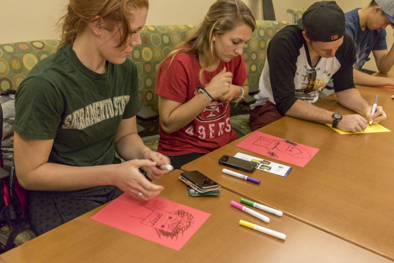 (Left to right) Jaden Garrett, Alexis Taber, and Chad Riley draw a physical embodiment of what their stress looks like in The Well on Tuesday, Oct. 20, 2015.