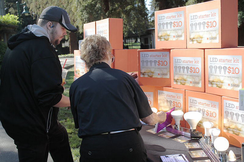 Carol Stout from SMUD (right) shows James Presley (left) SMUD's LED starter kit during Energy Conservation Day on Thursday, Oct. 9, 2015 at the library quad.
