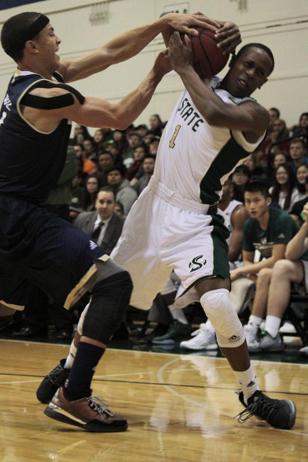 Lawrence White from UC Davis grabs the ball while Dreon Barlett stuggles to hold on during a game between Sacramento State and UC Davis on Tuesday, Nov. 24, 2015 at the Hornets Nest.