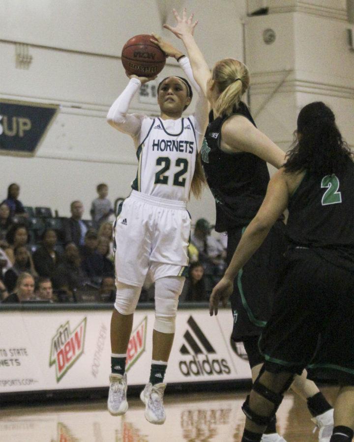 Sophomore Maranne Johnson goes for a shot over North Dakota's Samantha Roscoe. North Dakota won 86-79 on Feb. 27 at the Nest.