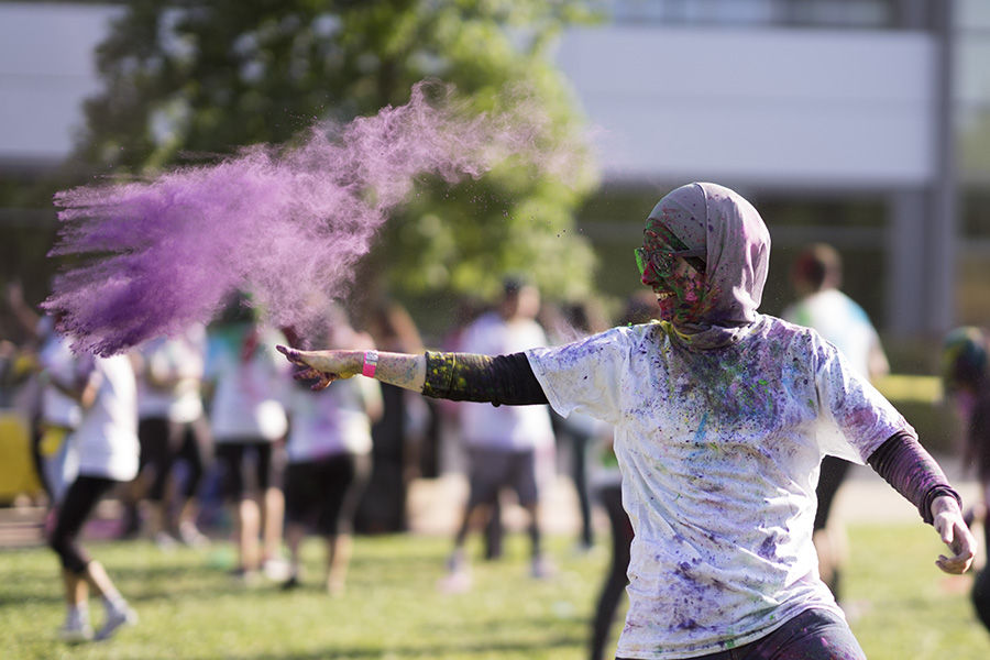 A Sacramento State student throws colorful powder during the Hornet Holi event hosted by Bhagat Puran Singh Health Initiative (BPSHI) in the Well front lawn, Friday, April 29.