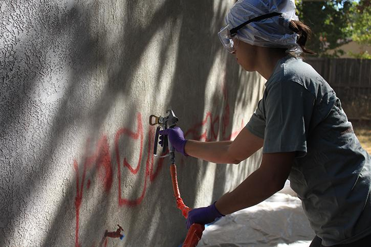Sac State student Nicole Silva paints over graffiti on the side of a house in Oak Park during the Paint the Town event on Saturday, Sept. 17. (Photo by Barbara Harvey)