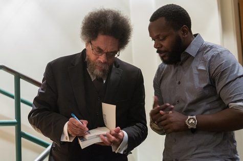 "Cornel West signs a copy of his book ""Race Matters"" for graduate student Antoine Johnson during West's visit to Sacramento State on Thursday, Sept. 29. ""He's one of the remaining writers that I look up to,"" Johnson later said. (Photo by Francisco Medina)"
