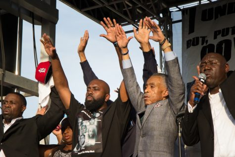 Michael Brown Sr., second from left, with Rev. Al Sharpton, second from right, as Attorney Benjamin Crump leads a call and response of