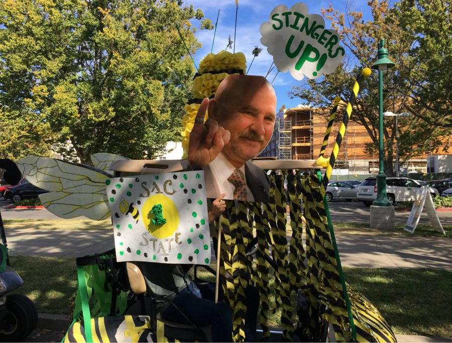 The College Assistance Migrant Program took home first prize with a cart designed with a cutout of President Nelsen in his signature stingers-up pose at Saturday night's 2016 homecoming parade. (Photo by Will Moon)