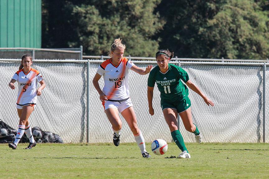 Sacramento State senior Jennifer Lum dribbles past Katherine Roberts of Idaho State at Hornet Field on Sunday, Oct. 9. (Photo by Matthew Dyer)