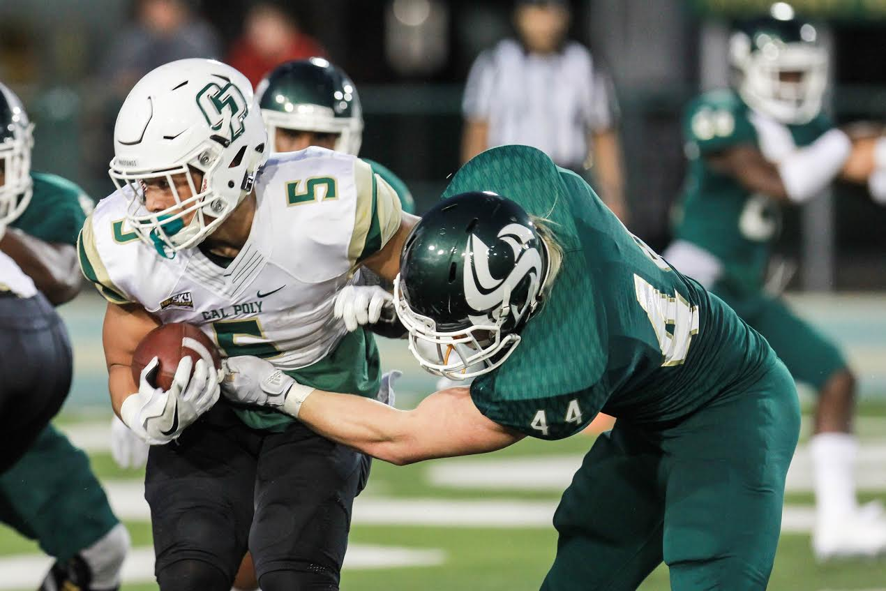 Sacramento State freshman linebacker Josiah Erickson attempts to bring down Cal Poly fullback Joe Protheroe on Saturday at Hornet Stadium. (Photo by Francisco Medina)