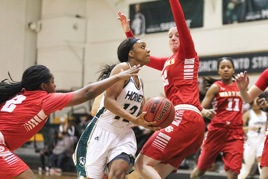 Sacramento State senior guard Ashlyn Crenshaw drives past two Stanislaus State players for a layup at the Nest on Tuesday, Nov. 29. (Photo by Matthew Dyer)