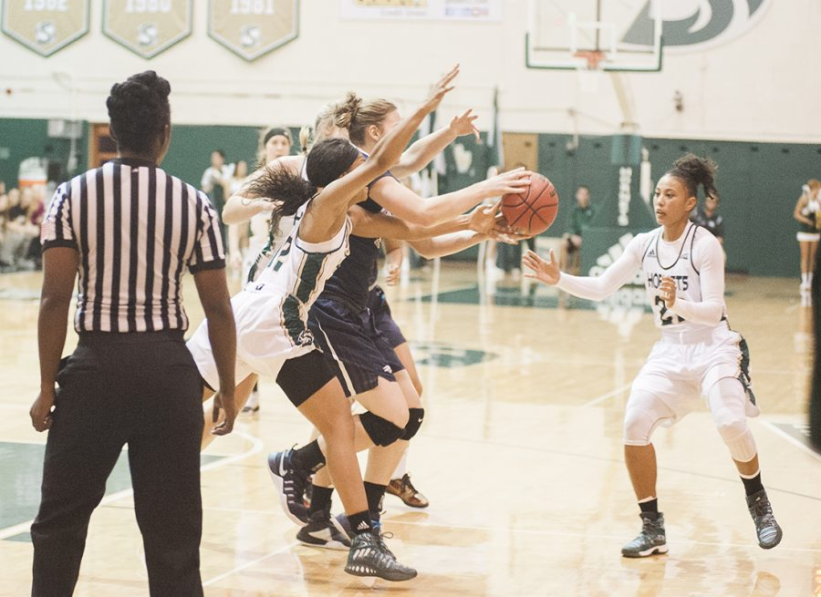 Sacramento State senior guard Ashlyn Crenshaw (12) and Maranne Johnson (22) try to grab the ball from a Nevada player on Wednesday, Nov. 16 at the Nest. Sac State lost 99-95 for its 11th straight loss to the Wolfpack. (Photo by Diana Rykun)