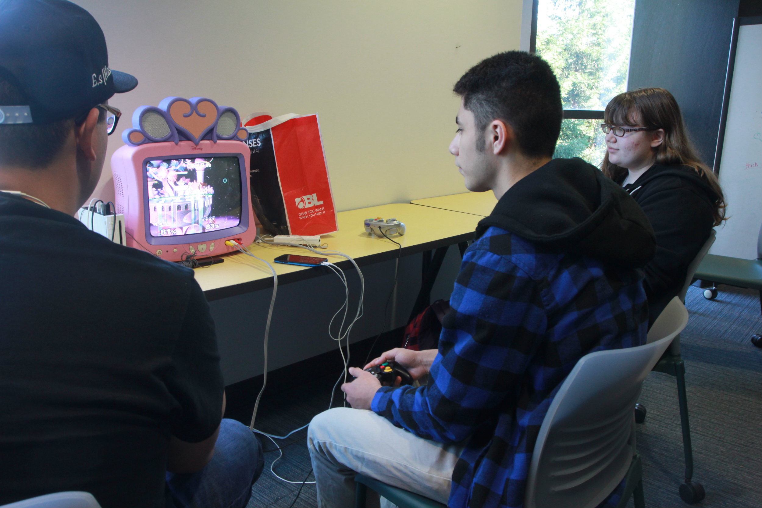 Members Allan Bona, left, and Alex Blanco, right, play the Super Smash Bros. Melee game on their pink TV on the third floor of the AIRC, Thursday, Nov. 3. (Photo by Harold Williams Jr.)
