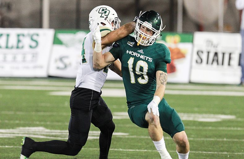 Sacramento State senior defensive back Nick Crouch rips through a Cal Poly offensive player's block at Hornet Stadium on Oct. 29. Crouch had five total tackles in the Hornets' 59-47 loss. (Photo by Francisco Medina)
