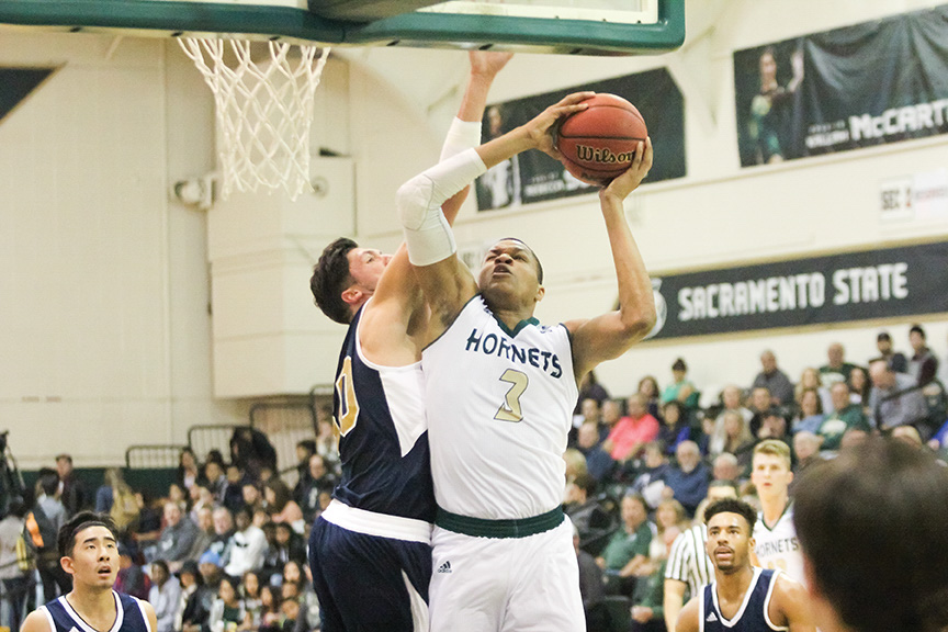 Sacramento State junior forward Justin Strings goes up for a layup against Ronnie Kozak of UC Merced at the Nest on Saturday, Dec. 3. (Photo by Matthew Dyer)