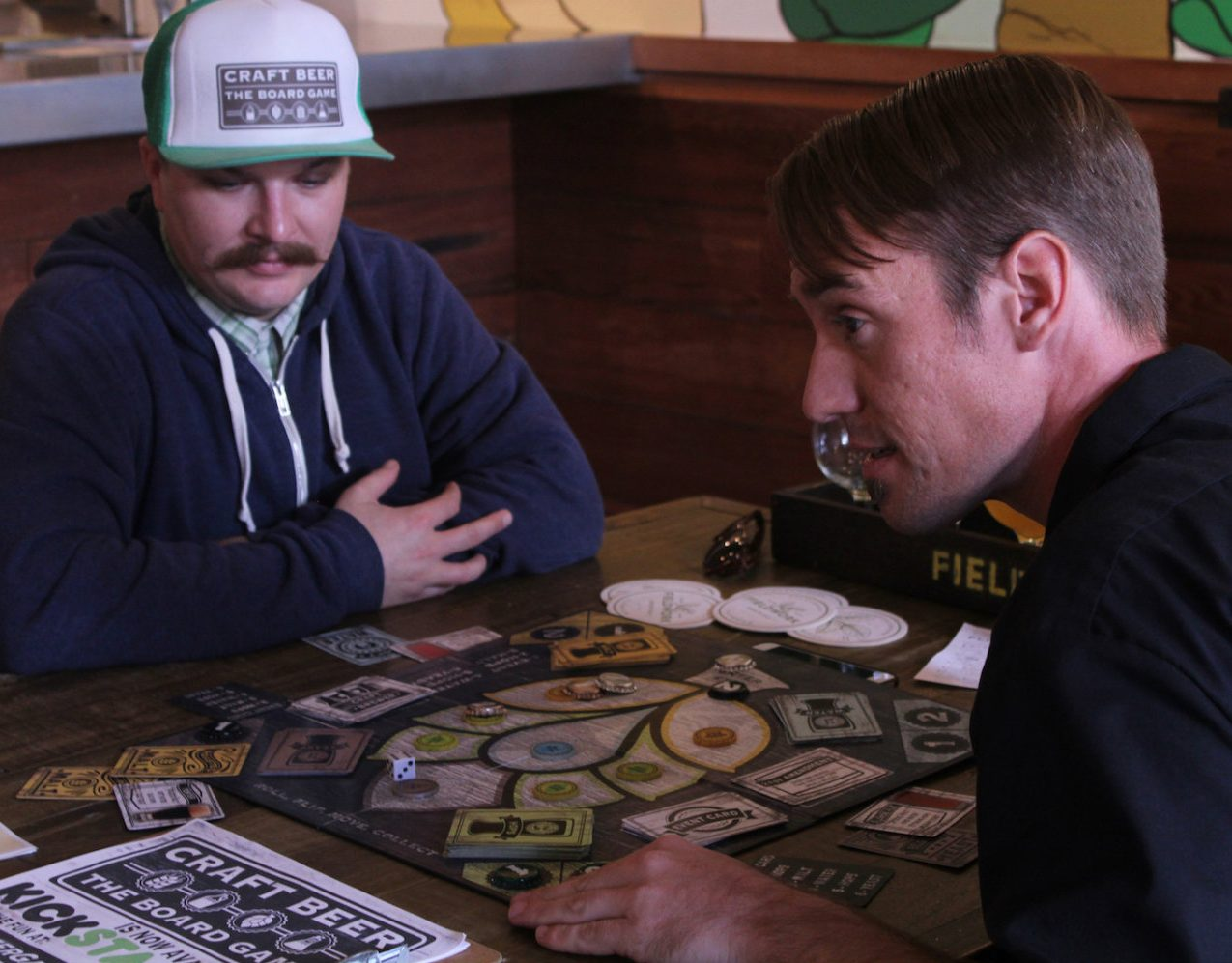 Sacramento State alumnus Collin Poseley, right, and his business partner Eric Foust, left, play the table top game they both created,