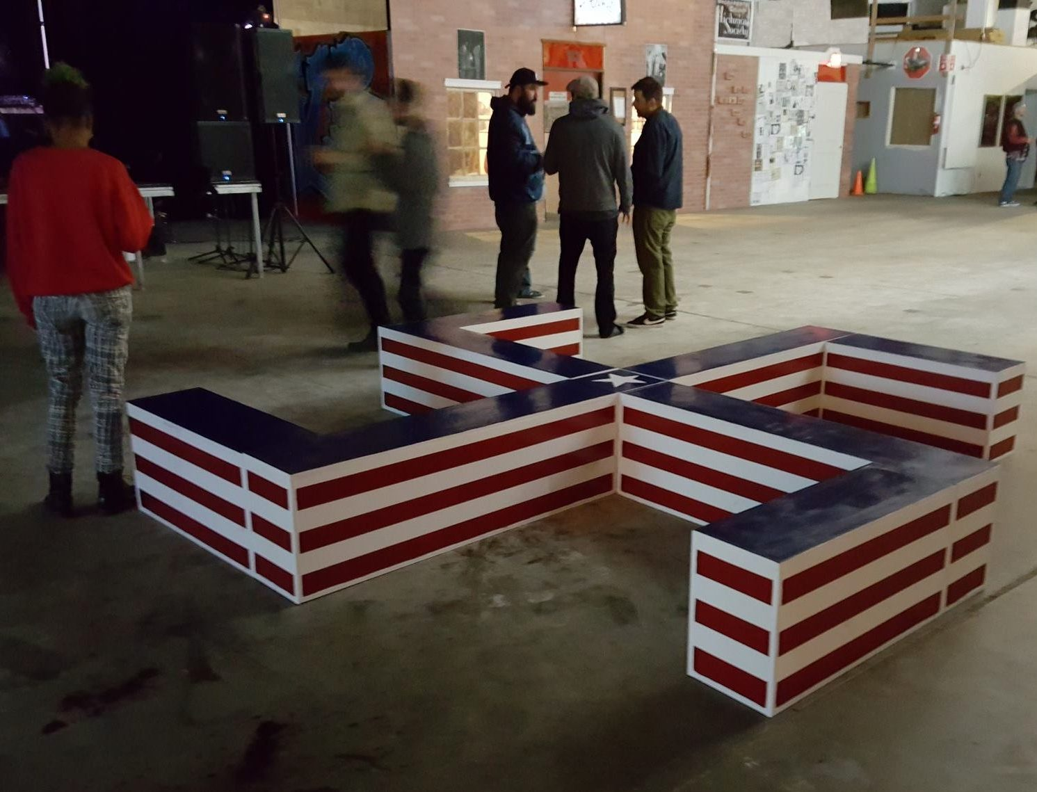 The wooden swastika-shaped bench painted with red, white and blue stripes was displayed at the abandoned warehouse on First Avenue — the location of ArtStreet — before being removed by the event coordinators. (Photo courtesy of Heston Hurley)