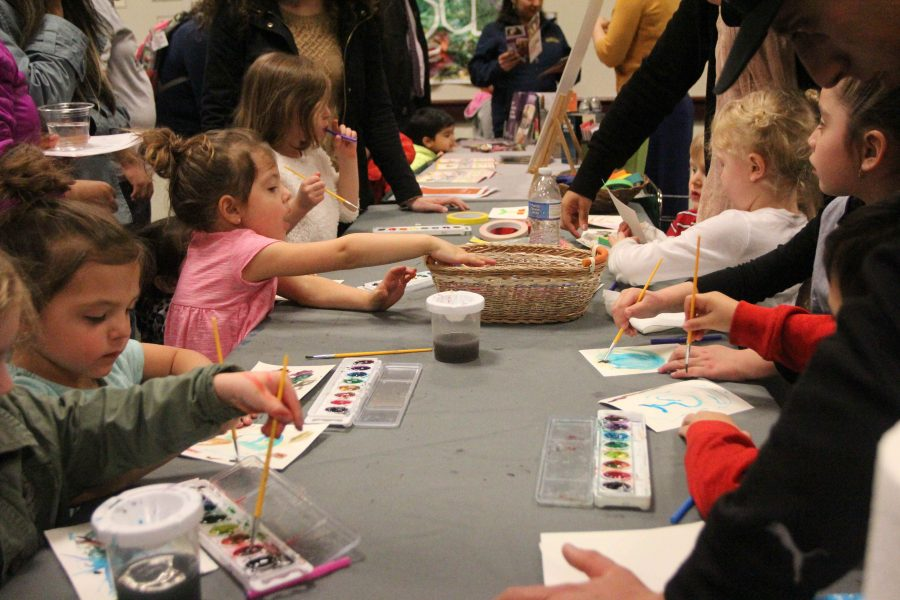 Children line a table, alternately paint with watercolors and blow through a straw on the watercolors as part of an interactive activity in the Orchard Suite during the 'More Than Just Scribbles' art reception on Feb. 23. (Photo by Rin Carbin)
