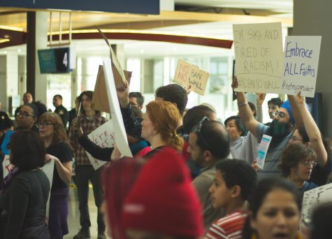 Protesters at the Sacramento International Airport on Jan. 29 hold up signs and chant slogans expressing disagreement with President Trump's executive order on immigrants and refugees. (Photo courtesy of Amer Tere)