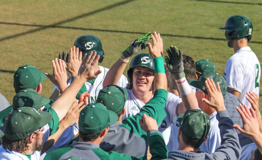 Sacramento State sophomore James Outman celebrates with teammates after scoring a run against Northern Kentucky at John Smith Field on Feb. 26. (Photo by Cameron Leng)