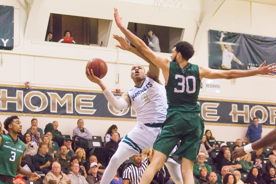 Sacramento State junior forward Justin Strings shoots the ball past Traylin Farris of Portland State at the Nest on Jan. 28.  Strings had 11 points and three rebounds for Sac State in a 80-77 victory. (Photo by Matthew Dyer)