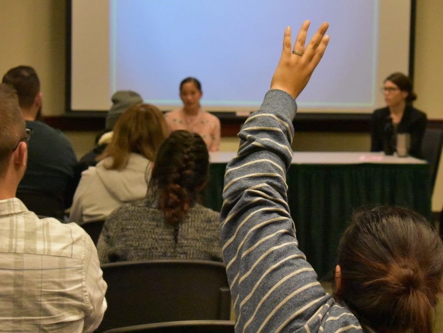 An attendee raises their hand to ask a question during a
