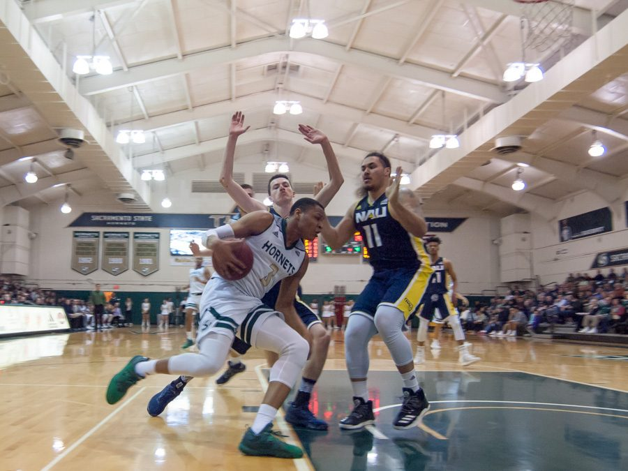 Sacramento State junior forward Justin Strings drives to the paint against two Northern Arizona players at the Nest on Thursday. (Photo by Andro Palting)