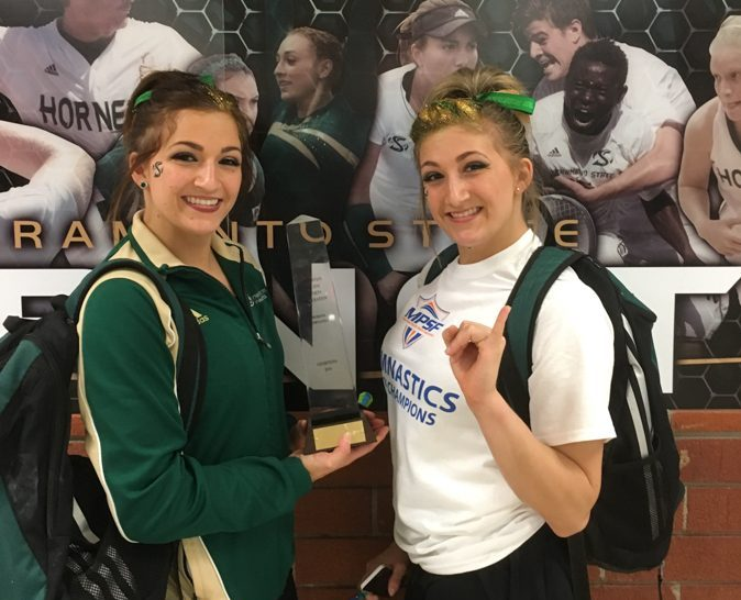 Sacramento State junior gymnasts Courtney and Caitlin Soliwoda show off the trophy after helping the Hornets win the Mountain Pacific Sports Federation Conference championship in 2016. (Photo courtesy of Courtney Soliwoda)