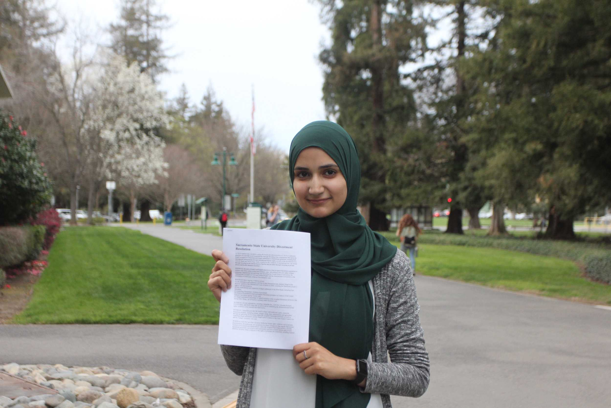 Aya Khalifeh, the president of Students for Justice in Palestine, holds a copy of SJP's divestment resolution, which calls for the CSU to let contracts with certain corporations expire. (Photo by John Ferrannini)