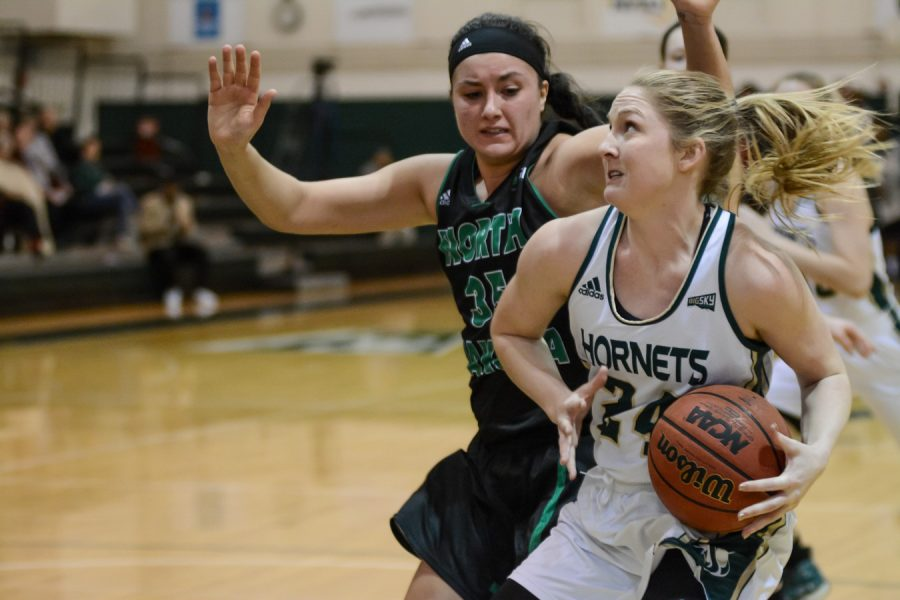 Sacramento State senior forward Gretchen Harrigan drives past Fallyn Freije of North Dakota for the basket Wednesday at the Nest. (Photo by Cassie Dickman)