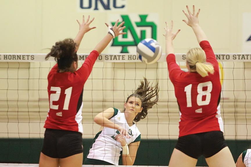 Sacramento State senior Madeline Cannon spikes the ball past two Eastern Washington blockers at the Nest on Oct. 22. The Sac State volleyball team will travel to China to play against youth, college and professional clubs in cities such as Beijing, Nanjing and Shanghai. (Photo by Matthew Dyer)