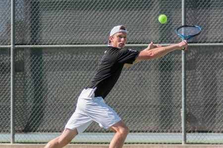 Sacramento State sophomore Dom Miller backhands the ball during a doubles match against Grand Canyon at the Golden State Invite at the Sac State Tennis Courts on Saturday, March 11. (Photo by Matthew Dyer)