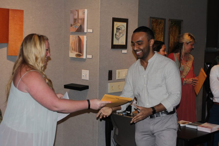 Mustafa Shaheen, right, receives the first prize award from Rebecca Voorhees, left, at the 42nd Student Purchase Awards reception. (Photo by Khanlin Rodgers)