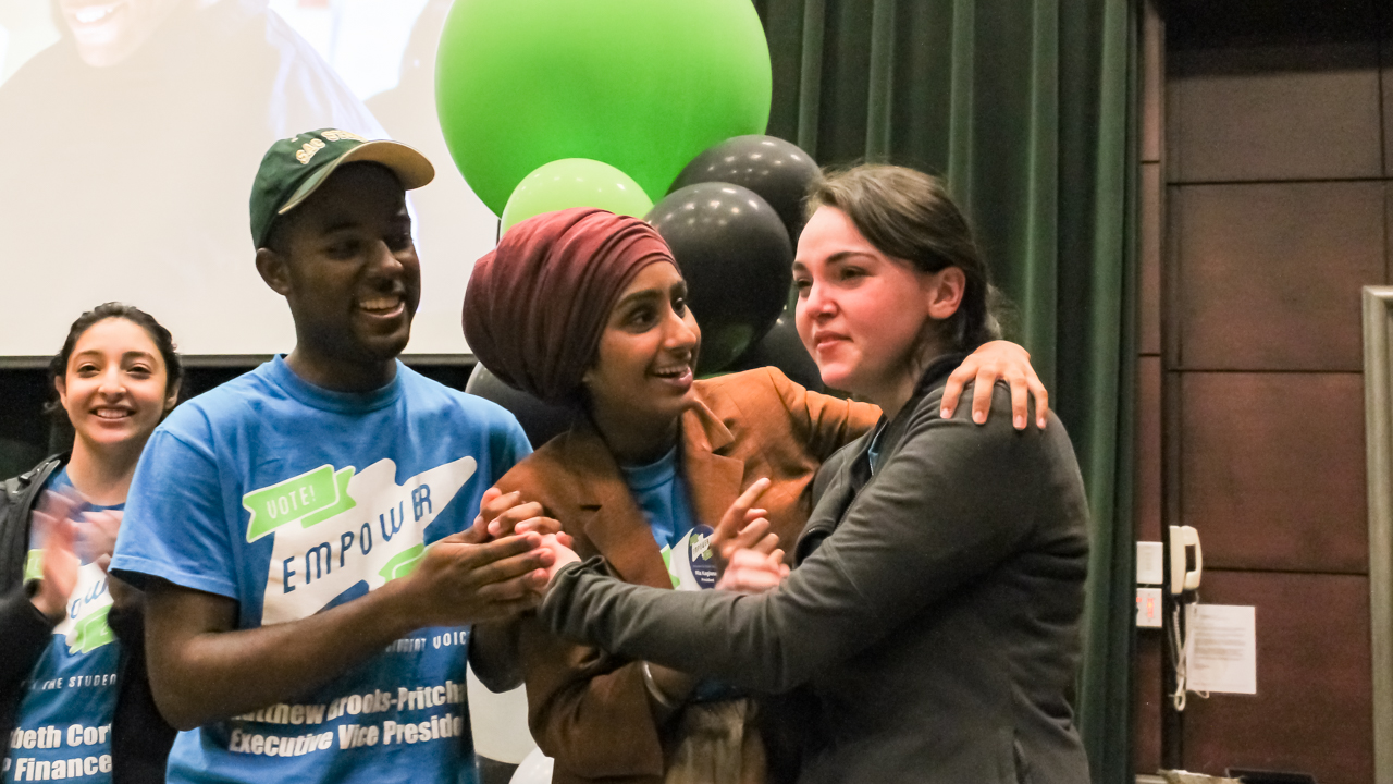 From right, Sacramento State junior Mia Kagianas embraces Karen Kaur Dhillon and Matthew Brooks-Pritchard after being revealed as the new ASI President at the ASI election results party in the Redwood Room in the University Union on Thursday, April 14. (Photo by Matt Lucas)