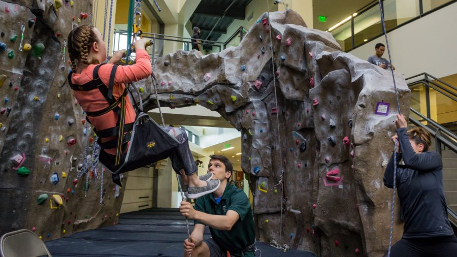 Sacramento State student Olivia Kite, left, assisted by Conner Marotte and RPTA volunteer Ashley Leyva, right, while using a pulley system to help her climb up the rock walls at The WELL. (Photo by Rin Carbin)