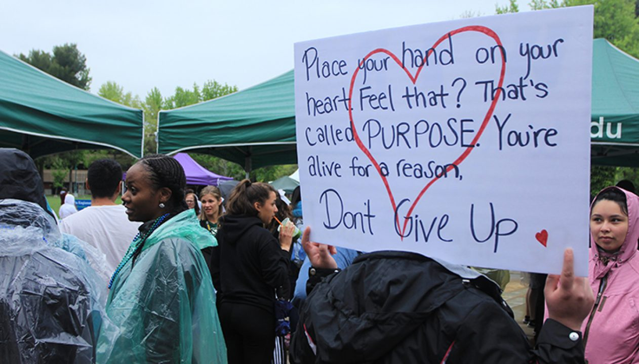 An attendee of the Out of the Darkness walk holds a sign they made on their shoulders.(Photo by Ricardo Coronado)