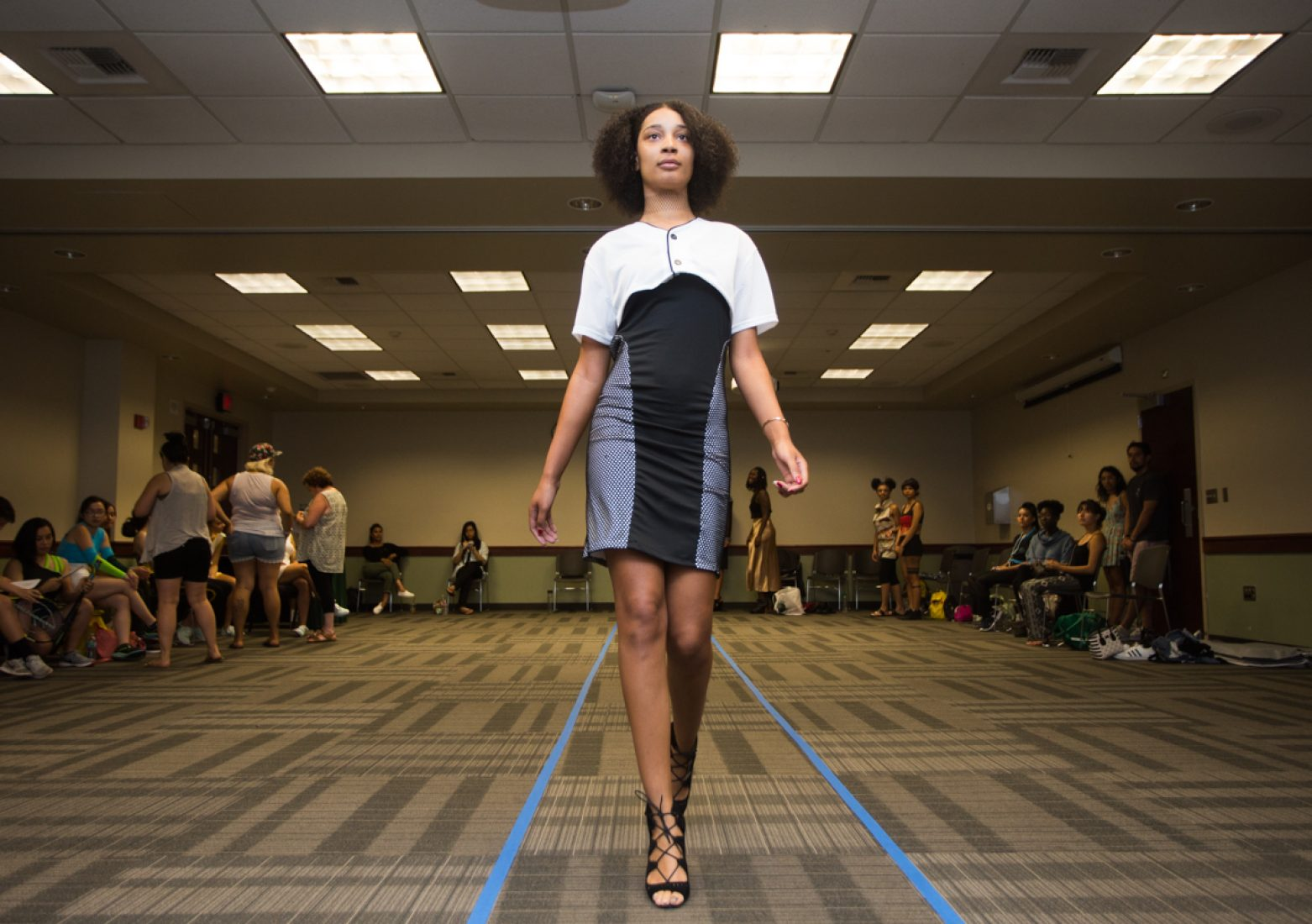 A model wears a cropped baseball jersey and a black mesh dress from designer Gabrielle Pyle during dress rehearsal in the University Union Foothill Suite on Wednesday. (Photo by Nicole Fowler)