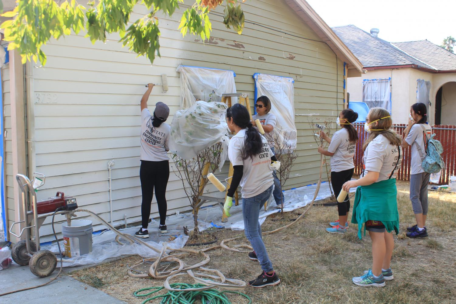 Sacramento State students from the Community Engagement Center paint houses at the 20th annual Paint The Town event in Del Paso Heights Saturday.