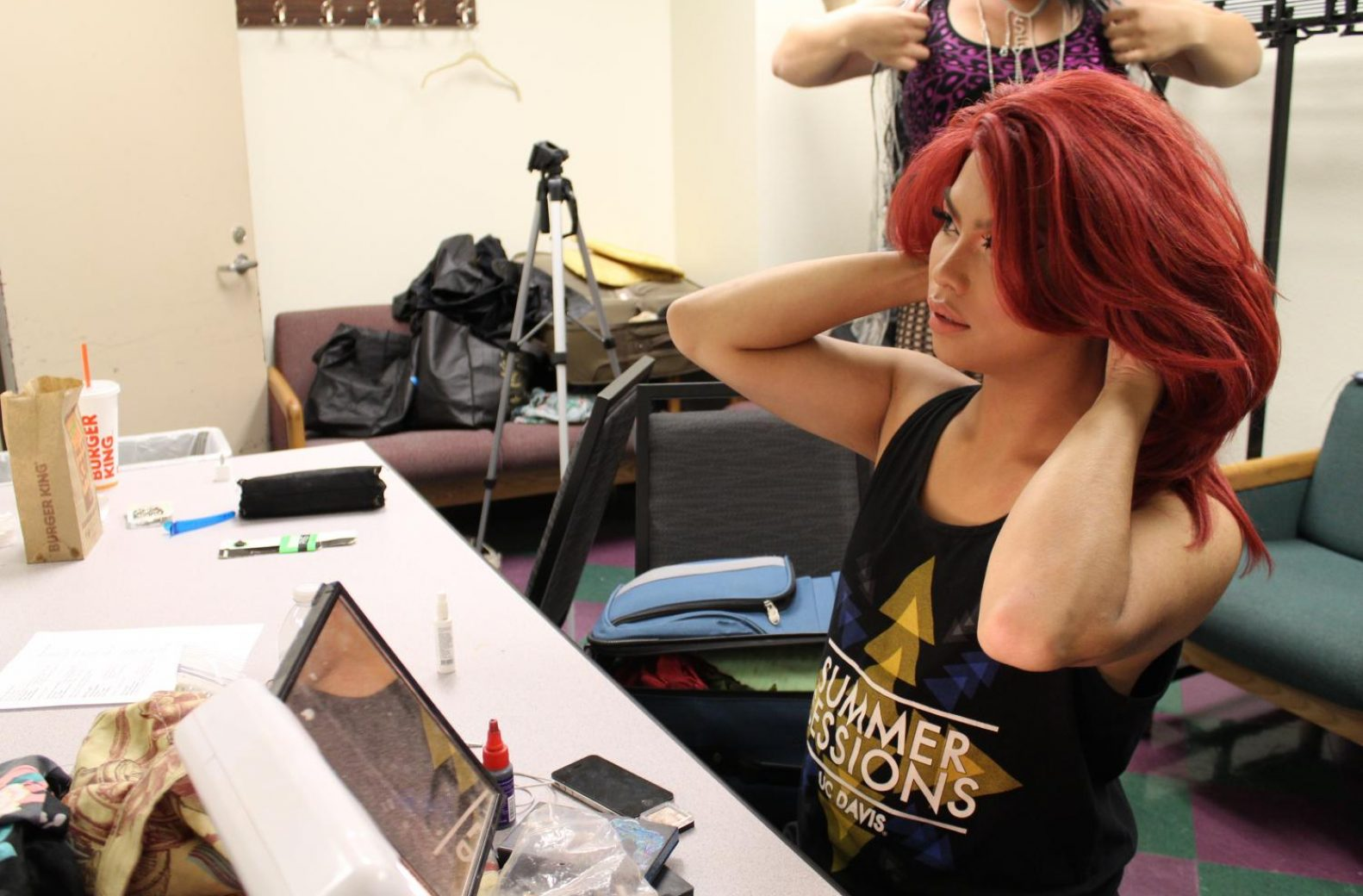 "Heidi Audacity, a Delta Lambda Phi brother from UC Davis's chapter, adjusts her red wig in the changing room before the ""Life is a Drag"" drag show, hosted by Sacramento State fraternity Delta Lambda Phi on Tuesday, Sept. 19. (Rin Carbin – The State Hornet)"