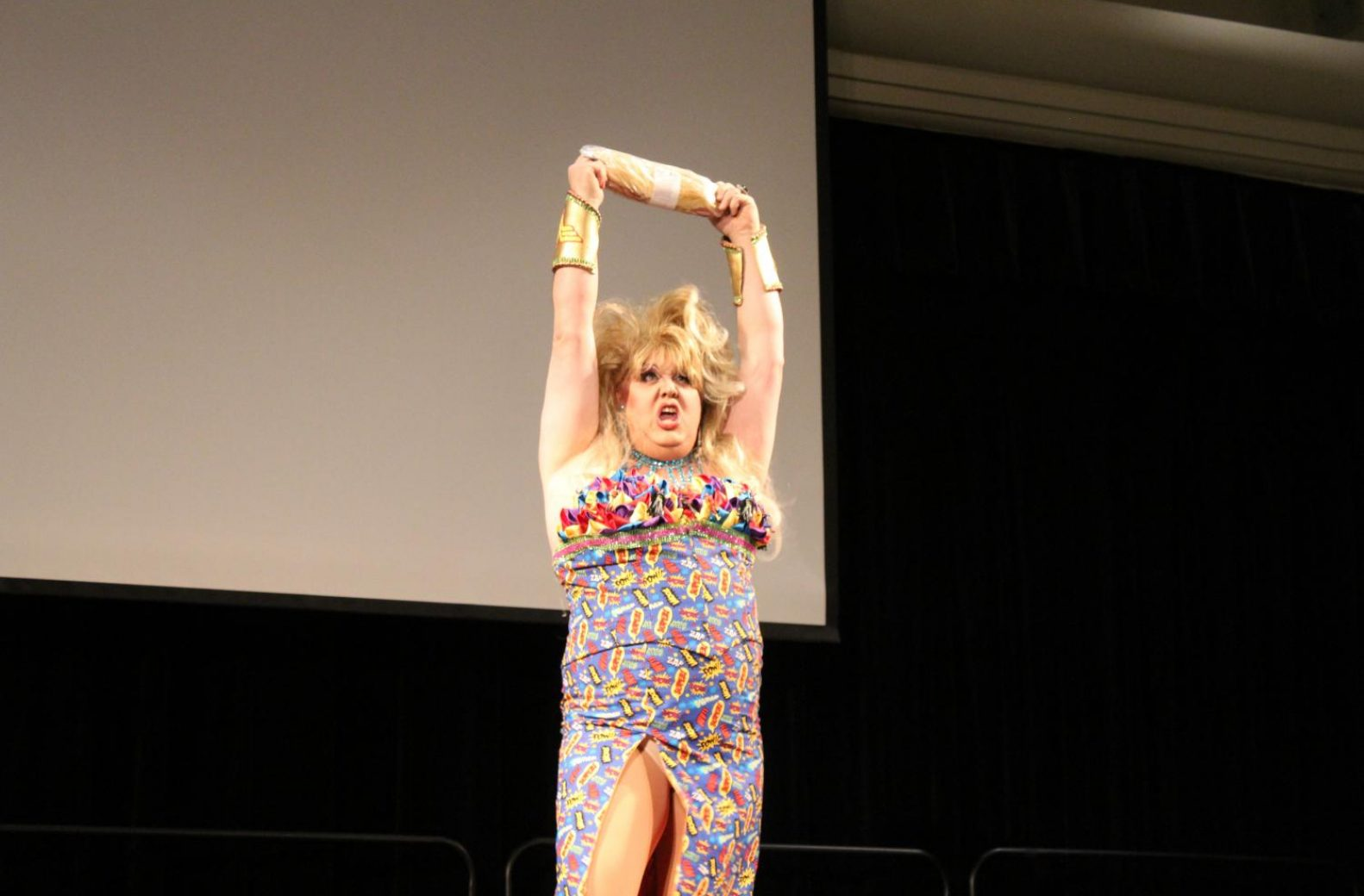"Haley Ricardo, wearing a superhero-themed dress, hefts a meat sandwich over her head during her lip-sync performance to ""Holding Out for a Hero"" by Bonnie Tyler. (Rin Carbin – The State Hornet)"