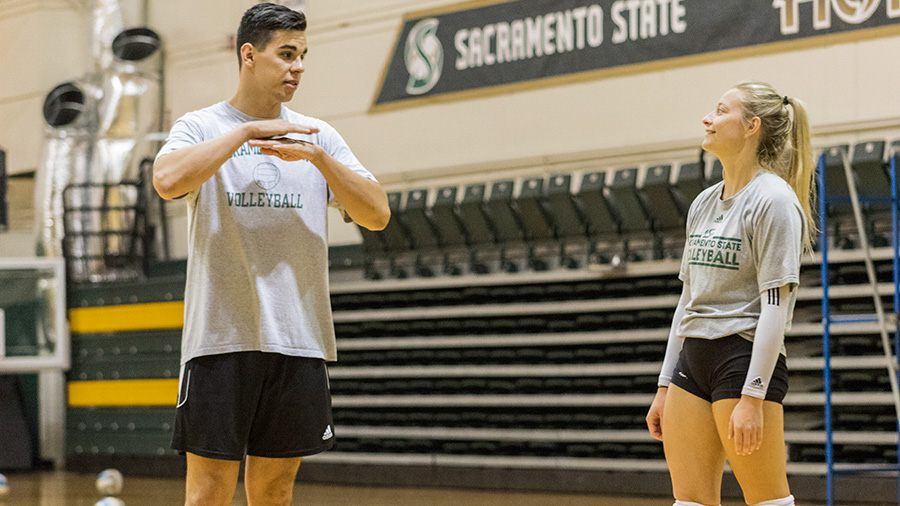 Sacramento+State+assistant+volleyball+coach+John+Fluette+instructs+senior+Julia+Wright+during+practice+Sept.+6+at+Colberg+Court.+Fluette+is+also+a+student+at+Sac+State+studying+environmental+studies.