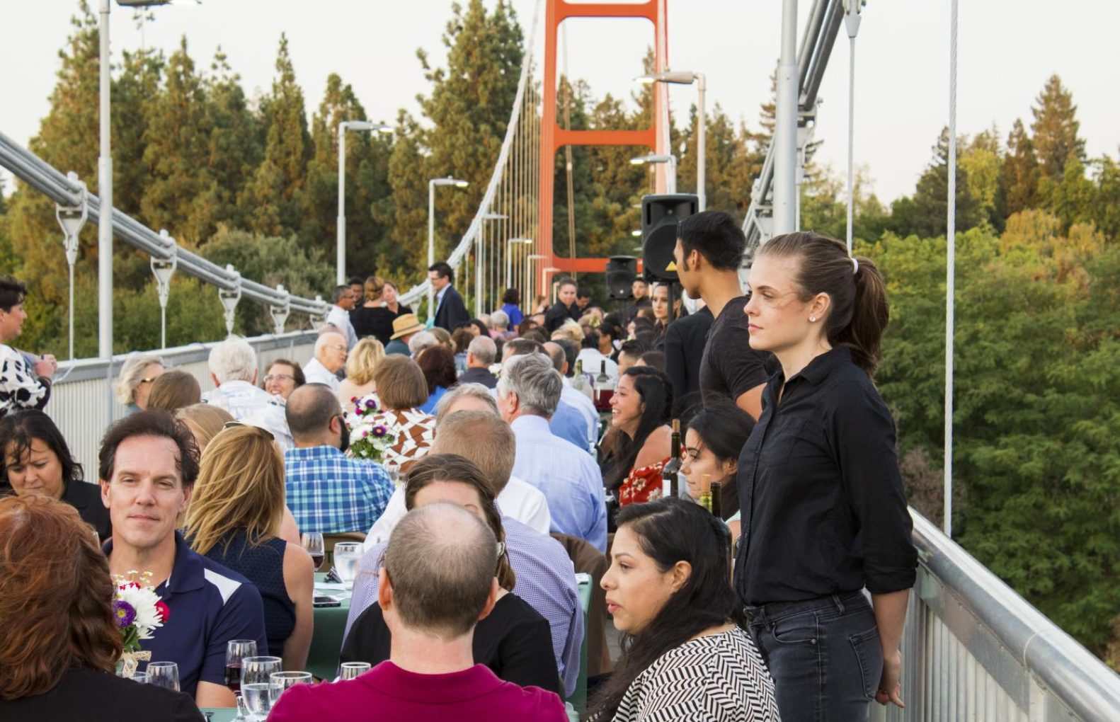 Guests of the second annual Sacramento State Farm-to-Fork dinner on the Guy West Bridge sit at their tables, waiting to be served by the student servers from on-campus restaurant Epicure on Wednesday. This year's dinner focused on the lives of farm laborers and their work. (Matthew Nobert – The State Hornet)