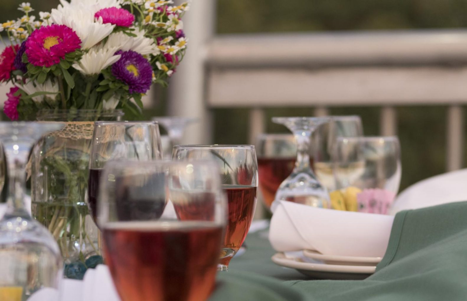Glasses of Muddy Boot red wine and flowers decorate the table of one of the tables during Sacramento State second Farm-to-Fork dinner on the Guy West Bridge on Wednesday. (Matthew Nobert – The State Hornet)