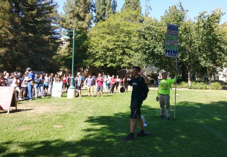 Sacramento State engineering major Slavik Chiley, far right, talks about his religious views in front of a crowd in the Library Quad on Sept. 27.