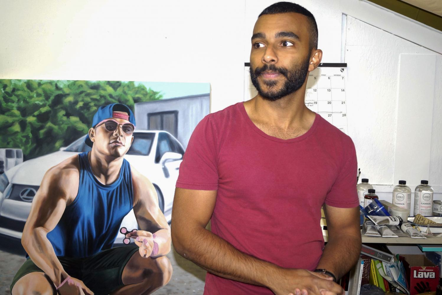 """Artist Mustafa Shaheen stands by """"Take the Red Pill,"""" his painting that represents Men's Rights Activists. Shaheen uses staged photos of his friends as models for the paintings, and often have them hold props like a fidget spinner. The painting is featured in his Advancement to Candidacy exhibit, """"Greetings from the USA,"""" which will be on display in the Robert Else Gallery from Oct. 16 - 20."""