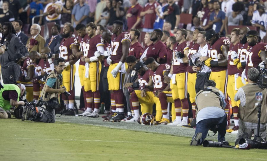The+Washington+Redskins+kneel+during+the+national+anthem+before+a+game+against+the+Oakland+Raiders.
