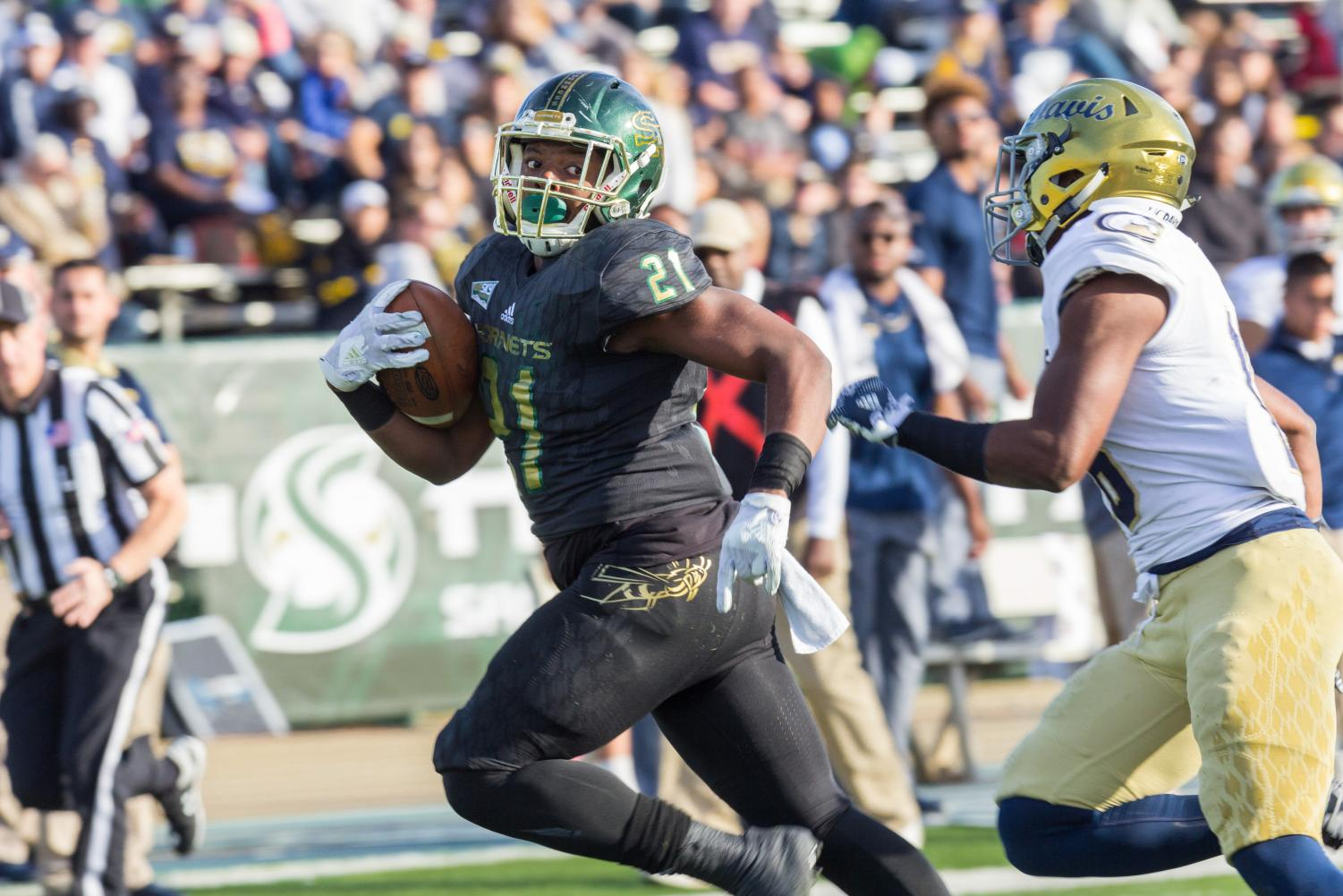 Sacramento State freshman running back BJ Perkinson sprints away from a UC Davis defender in the 64th annual Causeway Classic at Hornet Stadium on Saturday, Nov. 18, 2017. Sac State defeated the Aggies 52-47.
