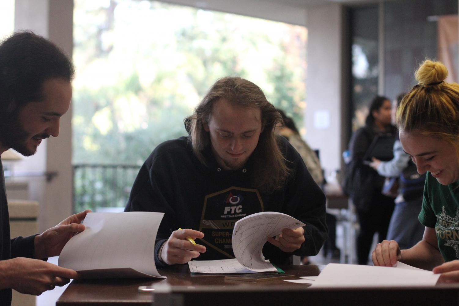 From left to right, Marco Bonanni, Timothy Hagen and Lauren Rice look over plans for their senior project on Dec. 1. They are among five students working on having parking tracking set up for Lots 9 and 10 by fall 2018.