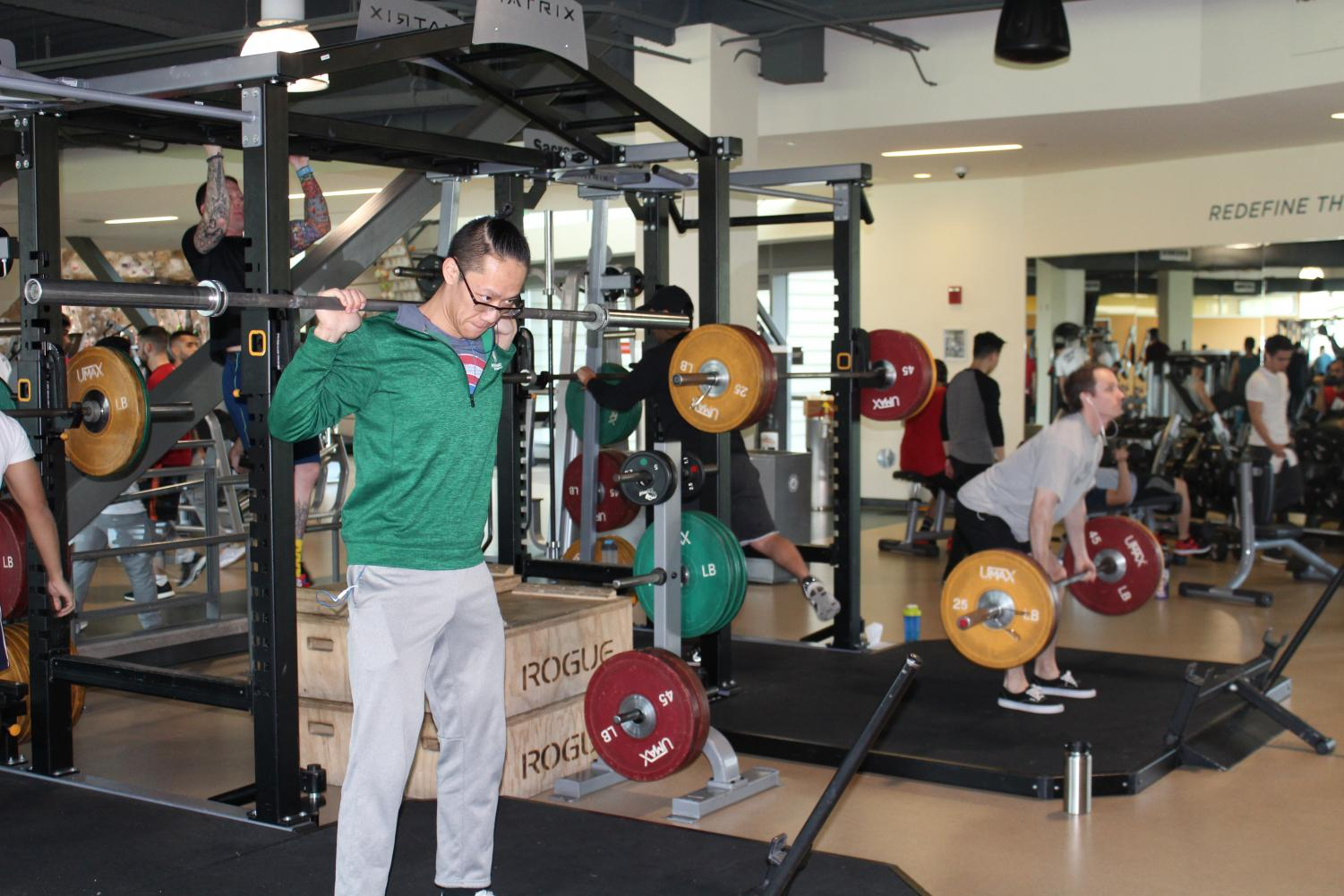 Sacramento State senior business administration major Willy Hoang, left, warms up with a barbell as he prepares for a squat session with the Sacramento State Stinger Barbell Club at The WELL.