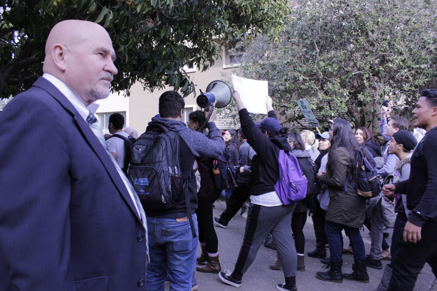 Students protesting the inaugration of President Donald Trump walk past Sac State President Robert Nelsen as he looks on. Those protests were cathartic, but protests of a tuition raise could make a real difference.